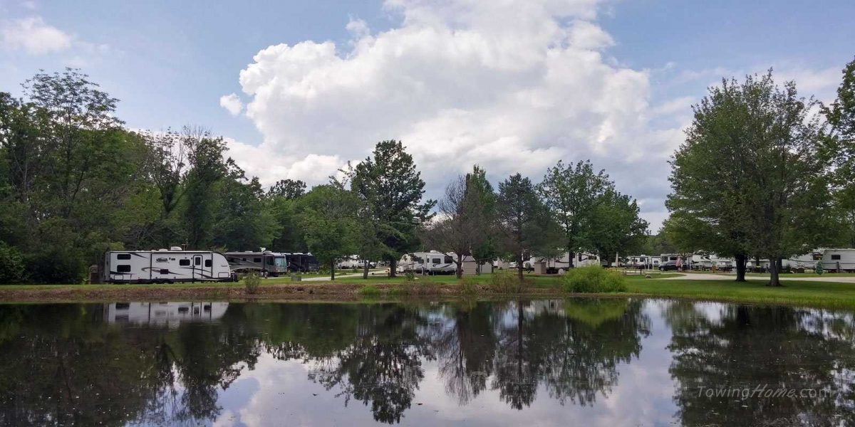 reflections of sky and trees in pond at rv park